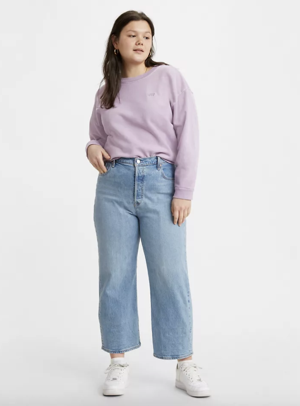 Model in light wash high waist jeans with wide boot cut bottoms
