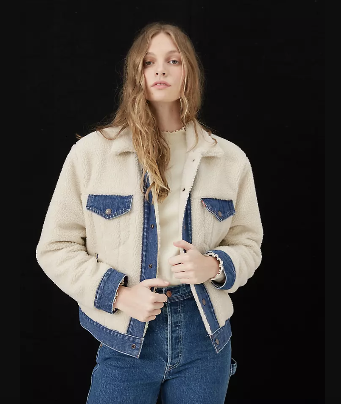 model in ivory trucker jacket with sherpa exterior and medium denim wash accents on pockets adn sleeves