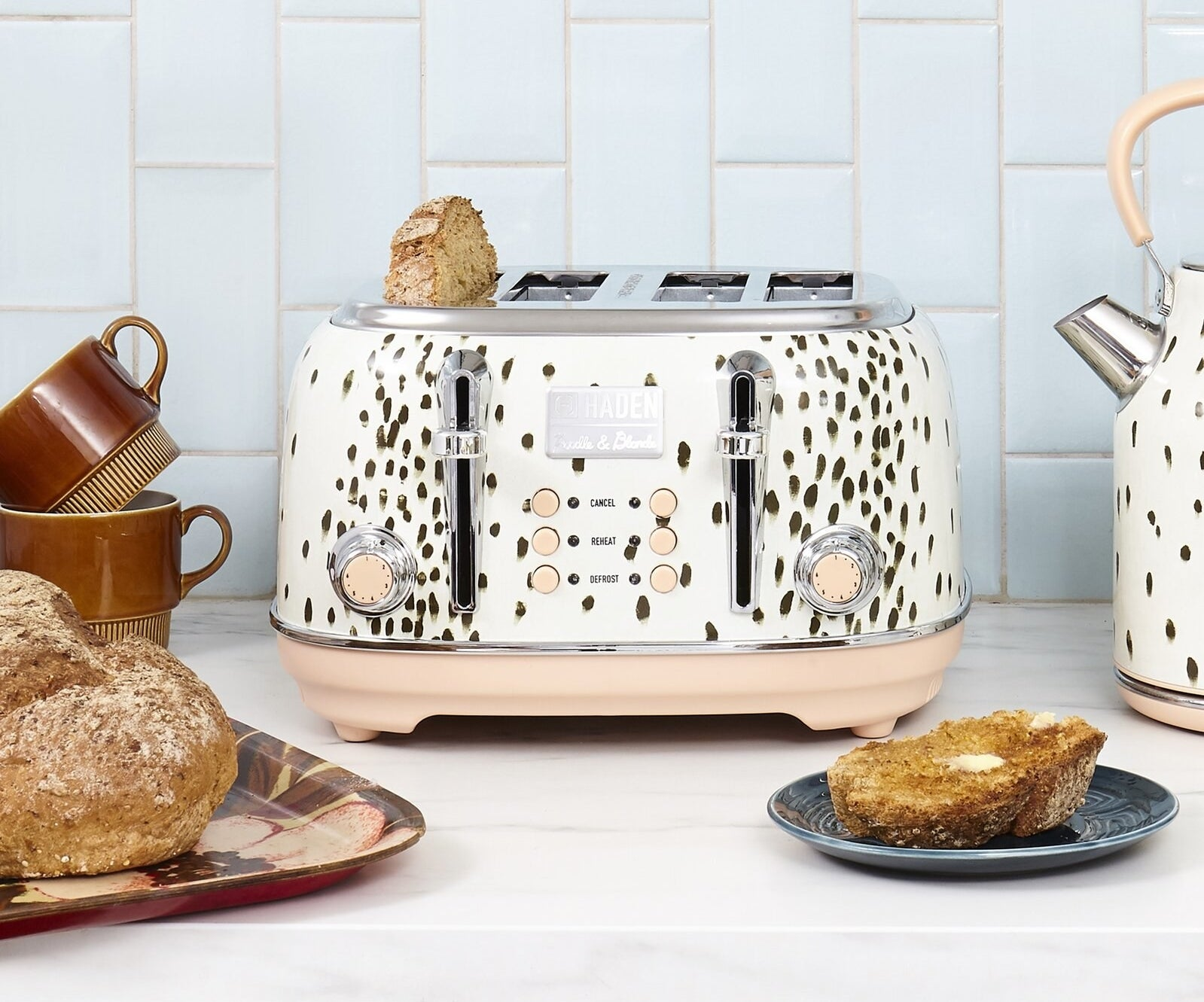 The four-slice toaster which has two dials, six buttons, and a black spotted finish