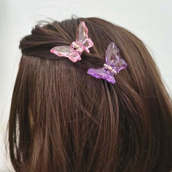 two plastic hair clips shaped like butterflies in hair