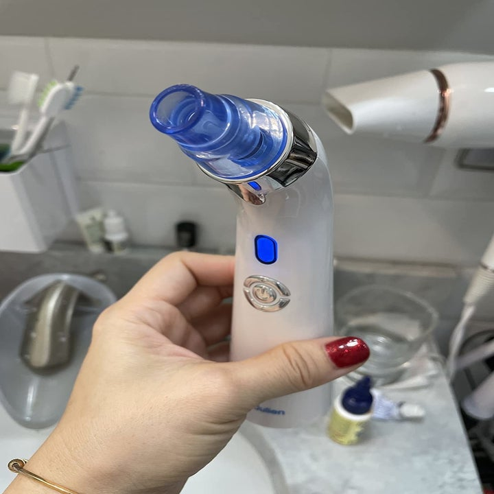 Reviewer holds black and white blackhead remover vacuum in hand
