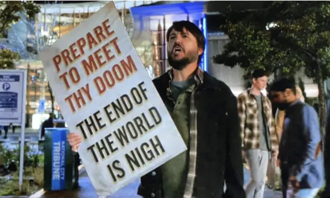 Will Wheaton holds a sign reading: prepare to meet they doom, the end of the world is nigh