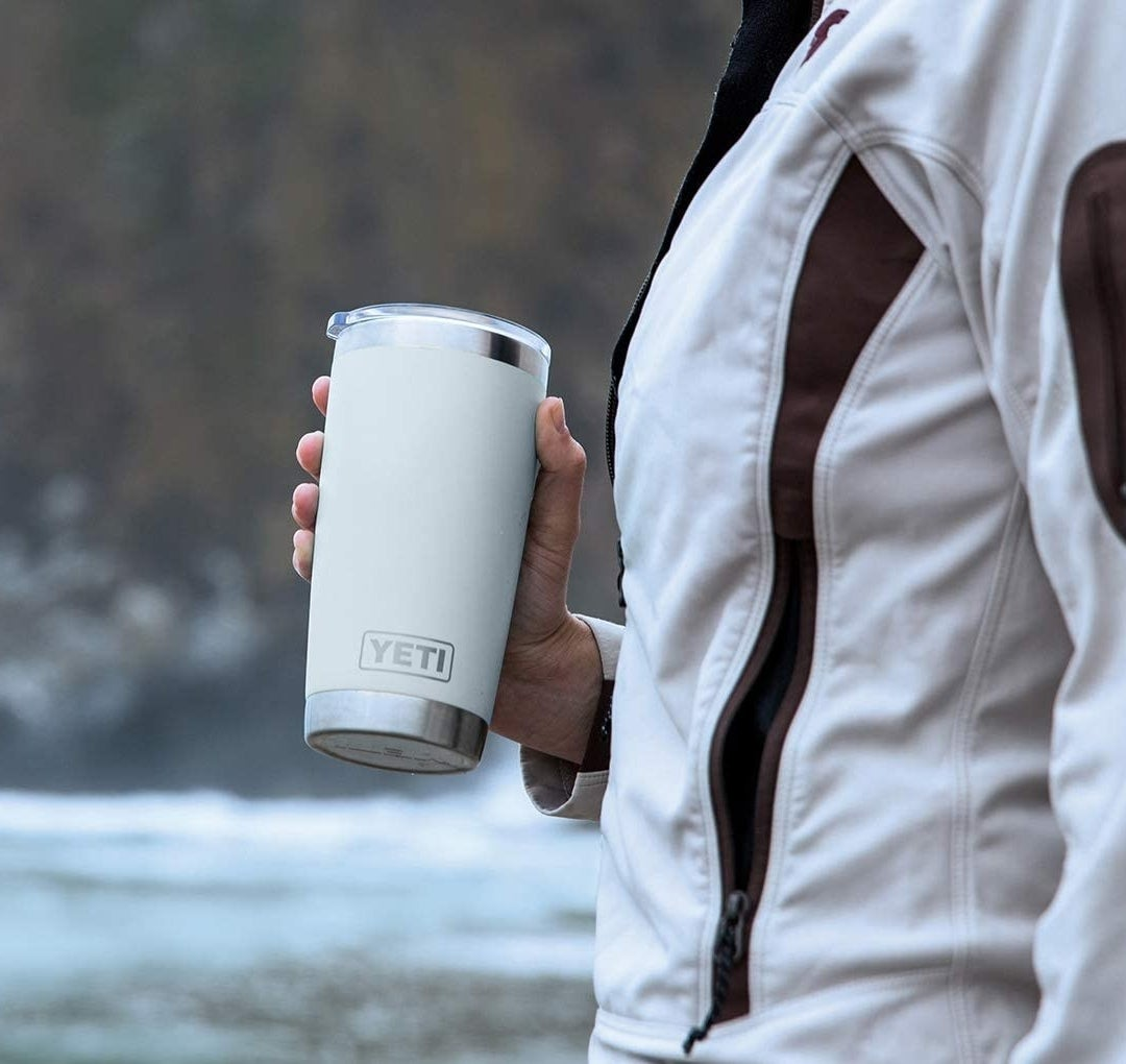 A person holding the tumbler outdoors
