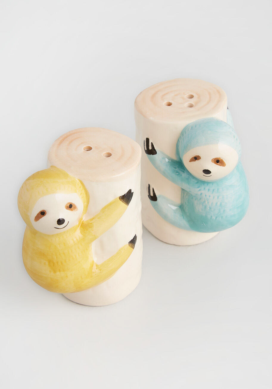 two cylinder shaped salt and pepper shakers with sloths hanging on the sides