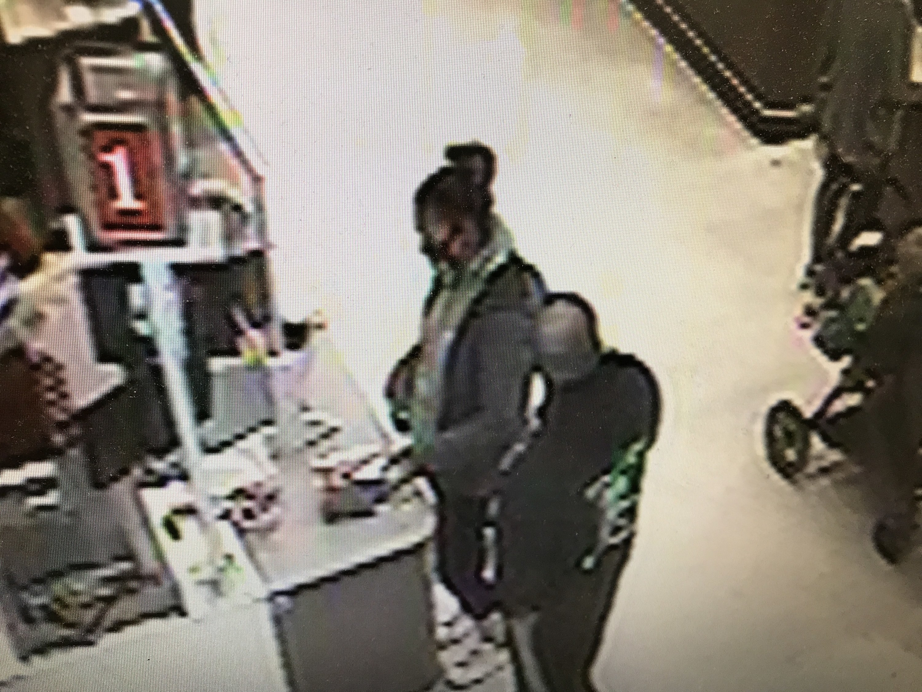 A security camera photo shows a man and woman standing close by at a checkout counter