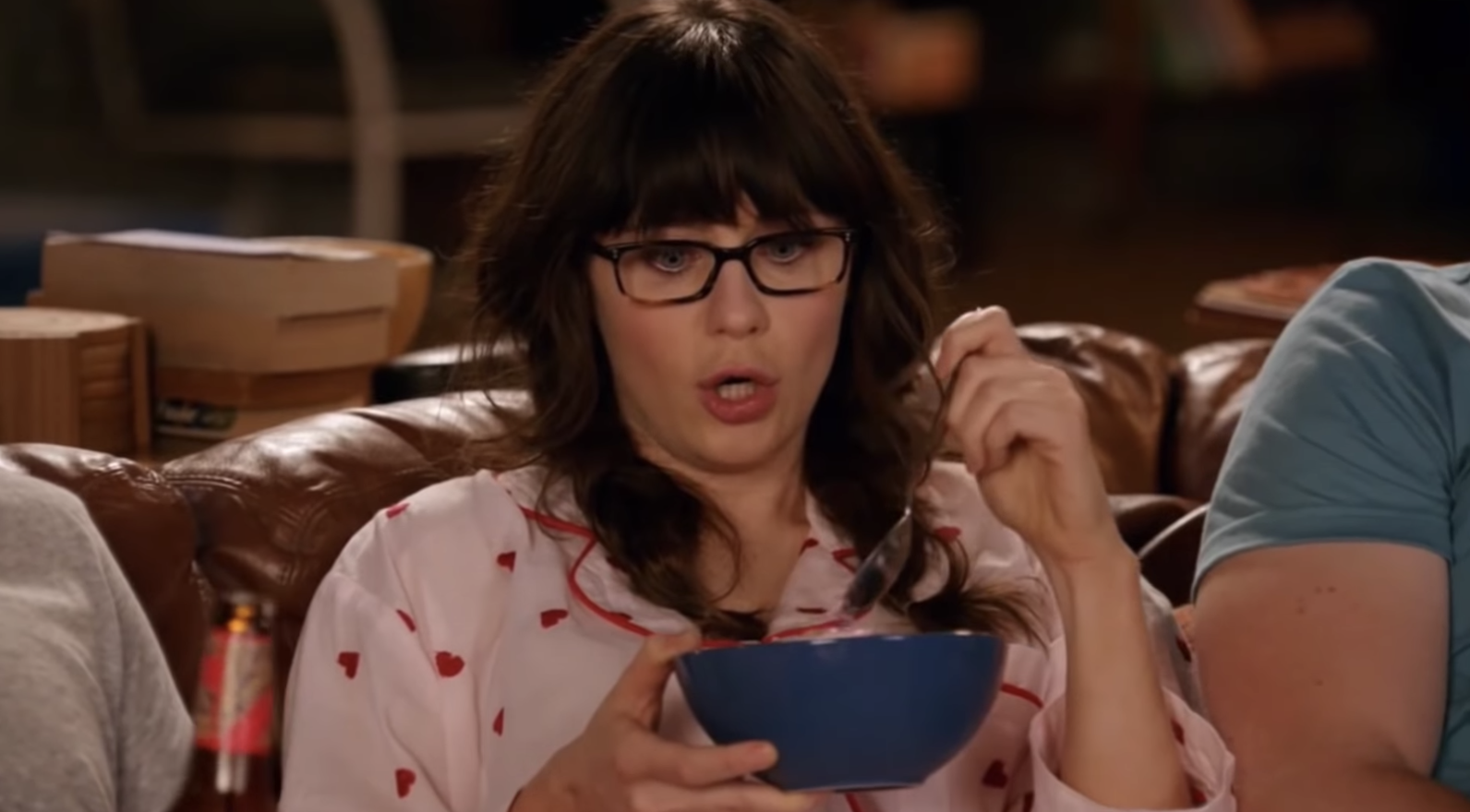 "Jess from ""New Girl"" eating ice cream on the couch while wearing glasses, pigtails, and a matching pajama set"