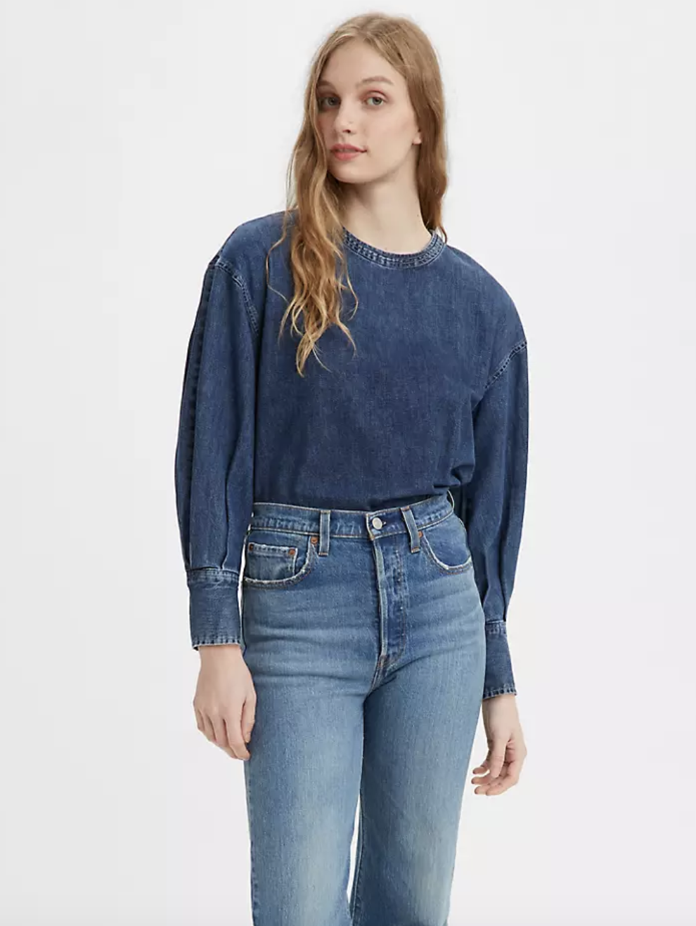 Model in a dark blue denim long sleeve blouse with puff sleeves