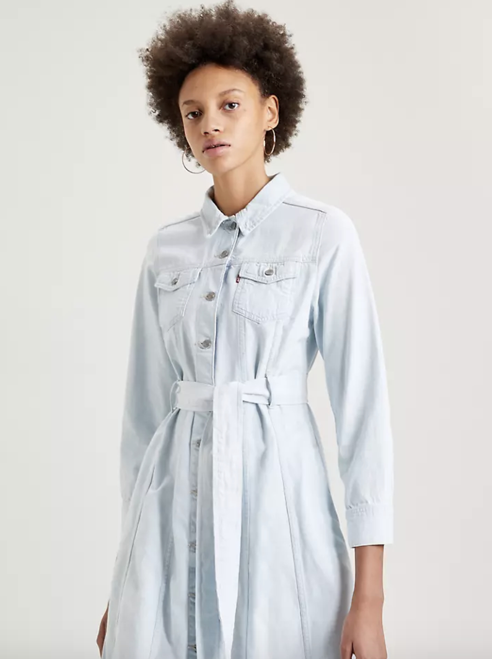 Model in pale light wash denim button up collared dress with tie string belt at waist and slight puff sleeves