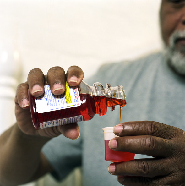 Image of a man pouring cough medicine.