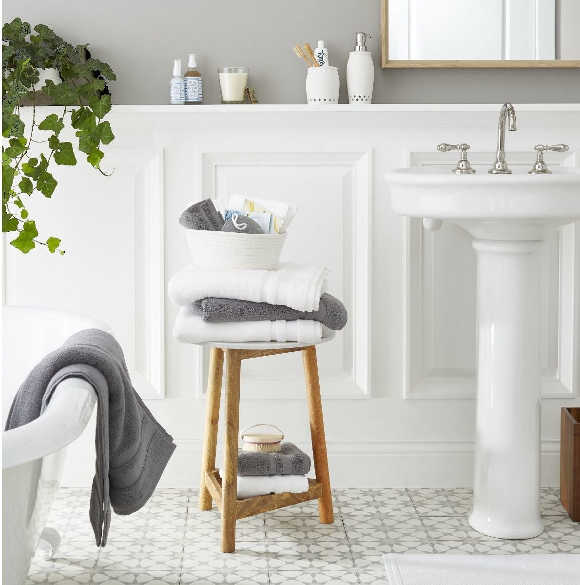 Wood and marble side table with gray and white towels stacked on top