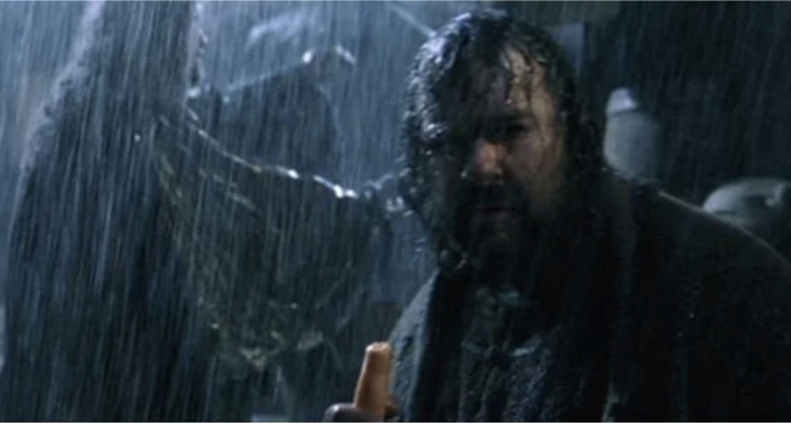 Peter Jackson stands in the rain among Lord of the Rings characters