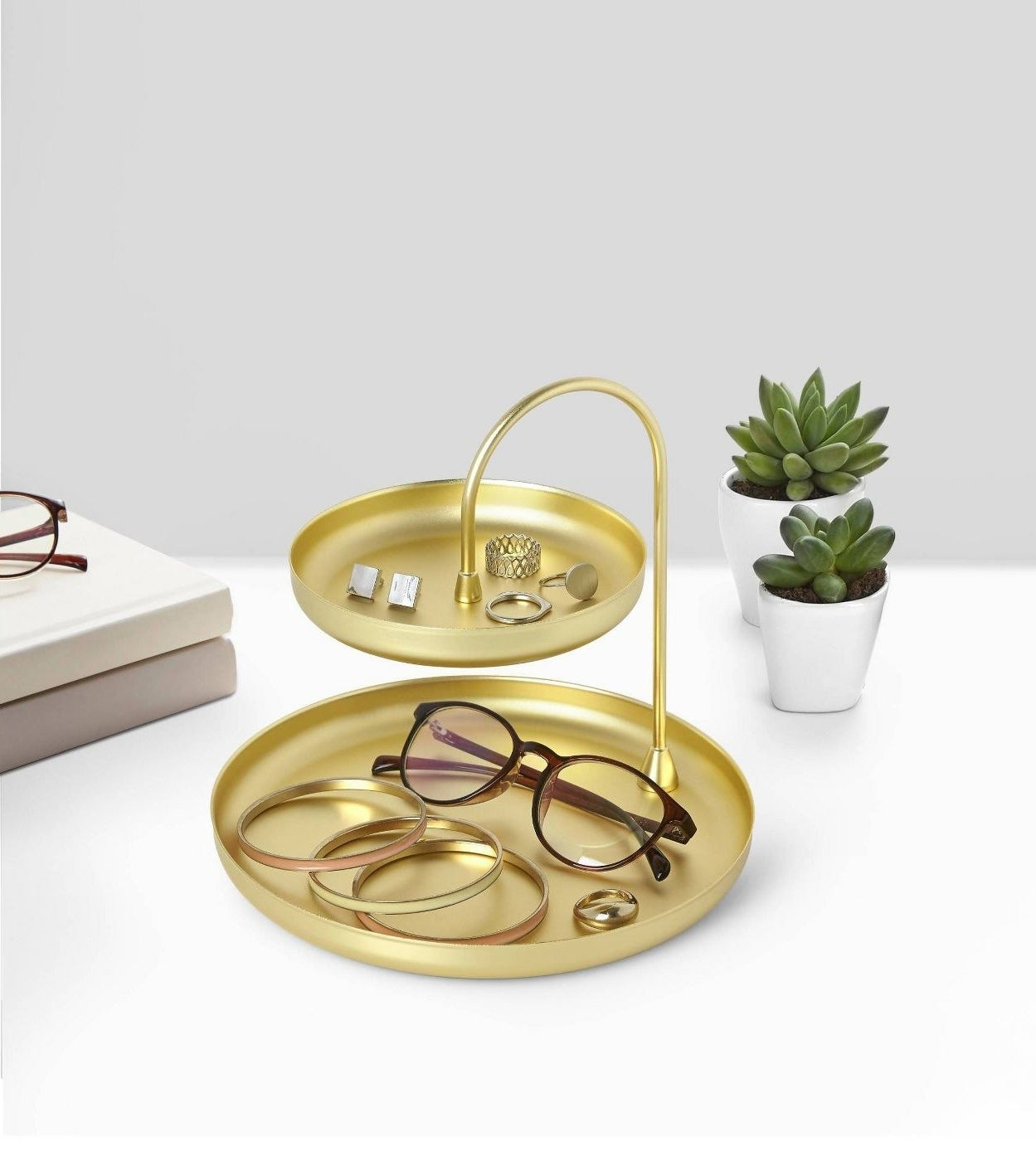 Brass two-tier tray displaying brown glasses, yellow, pink, and orange bracelets and gold rings.