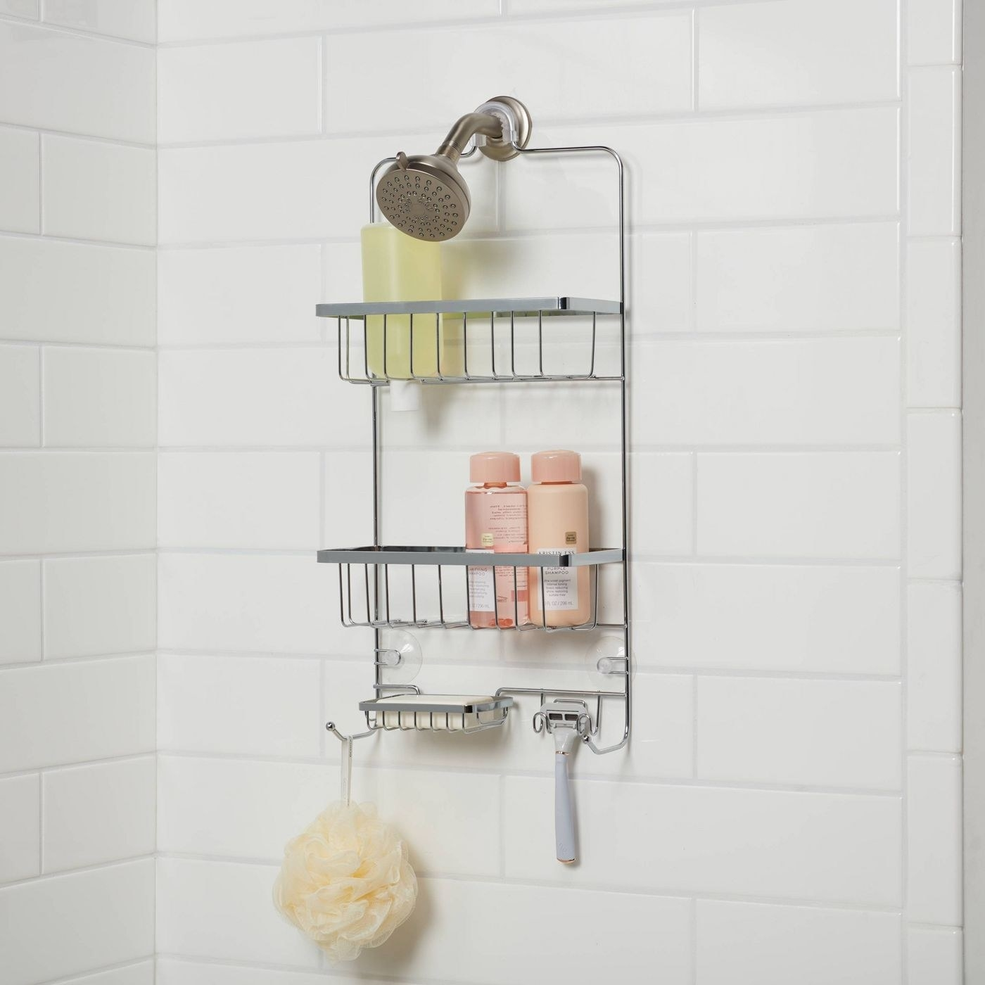 Chrome shower caddy with pink bottles and a pale yellow loofah