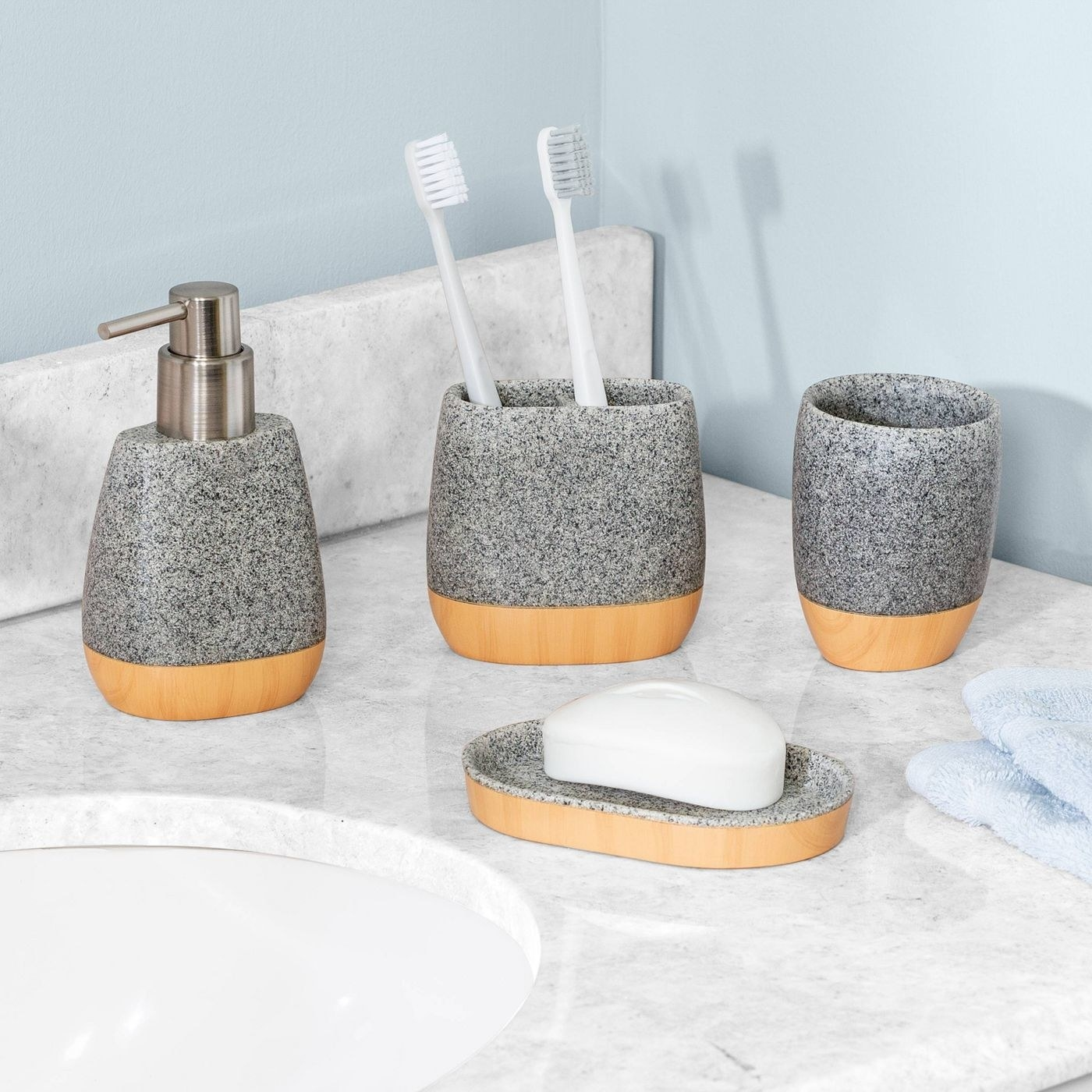 Gray speckled bathroom set with tan wooden bottoms displaying white toothbrushes and white soap