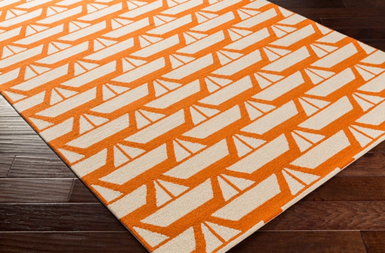 Orange rug with paper boat pattern throughout