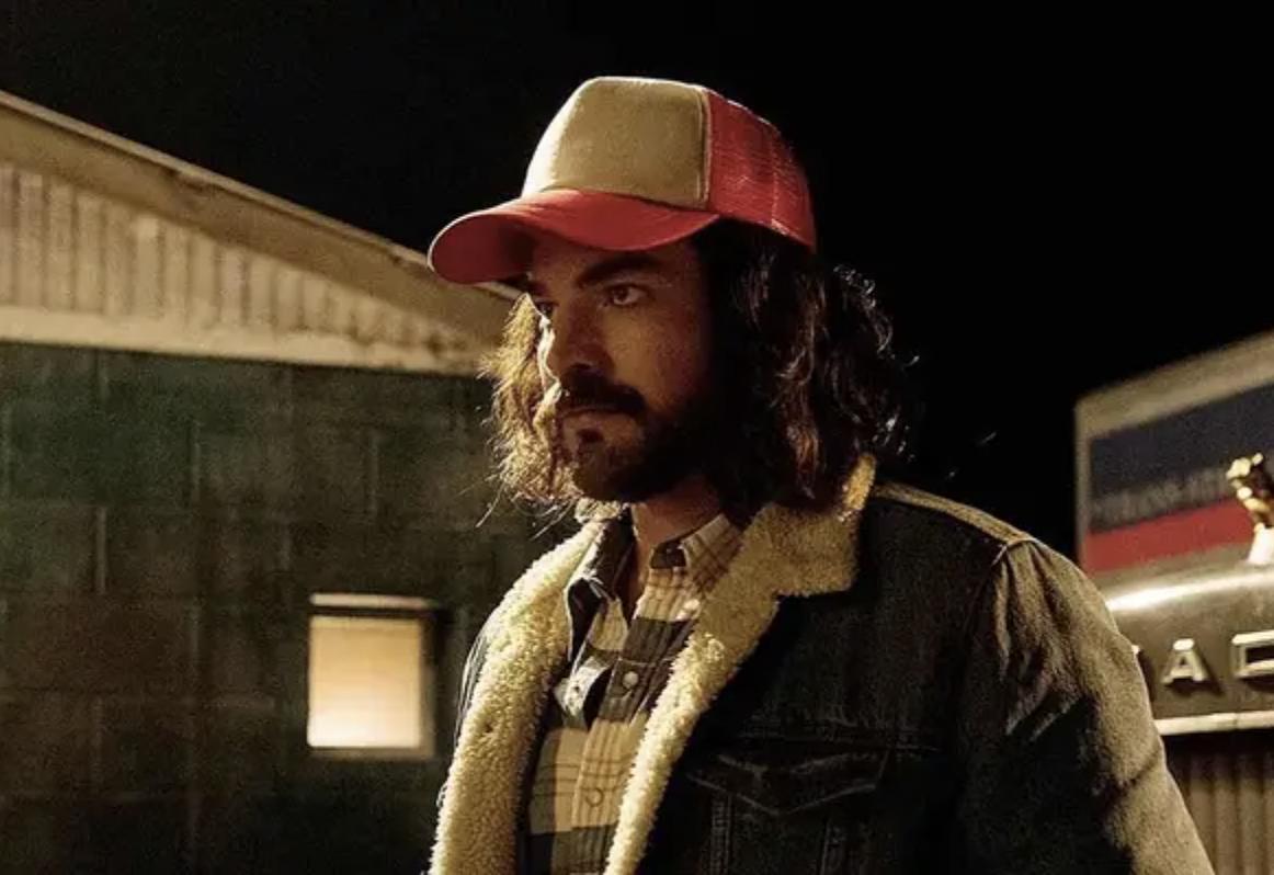 Adam Lambert wearing a trucker hat, long hair, and a scruffy beat