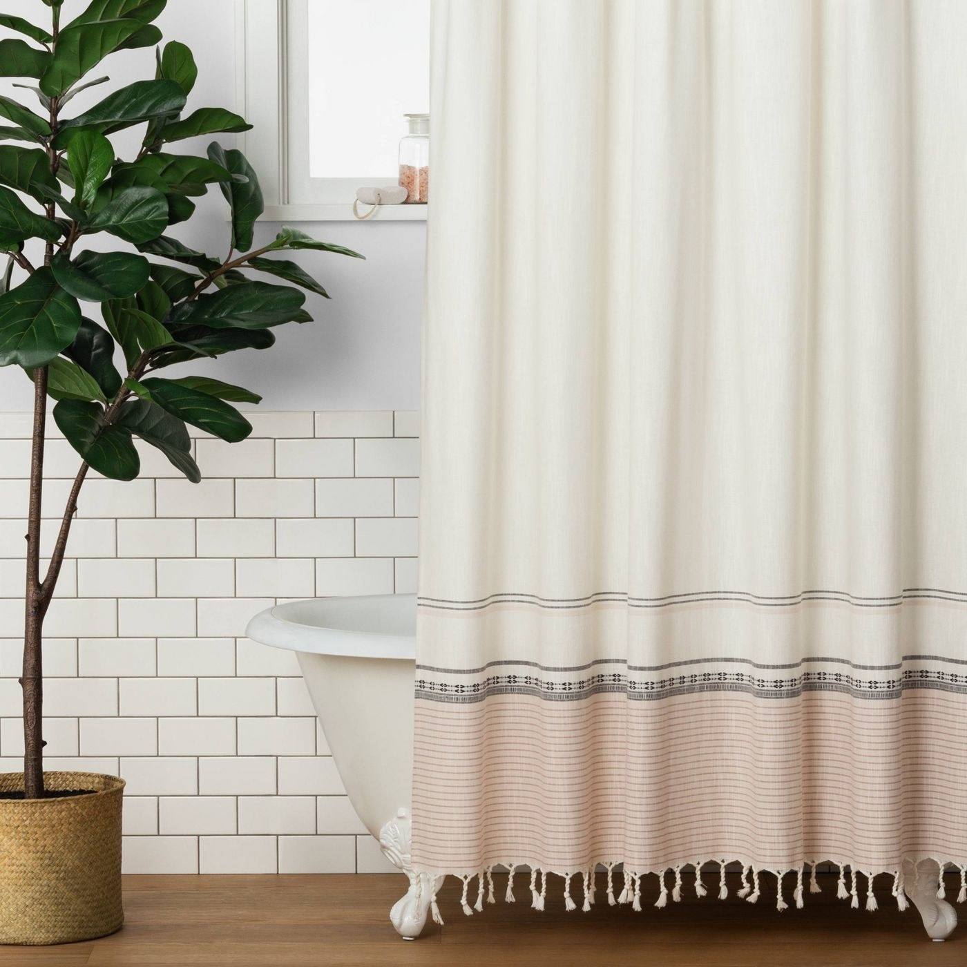 Cream shower curtain with pink bottom and dark gray detailing against a white tub and white wall