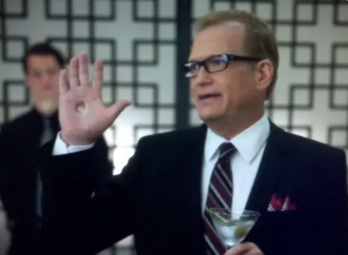 Drew Carey holds a martini in one hand while his other hand has a hole in it