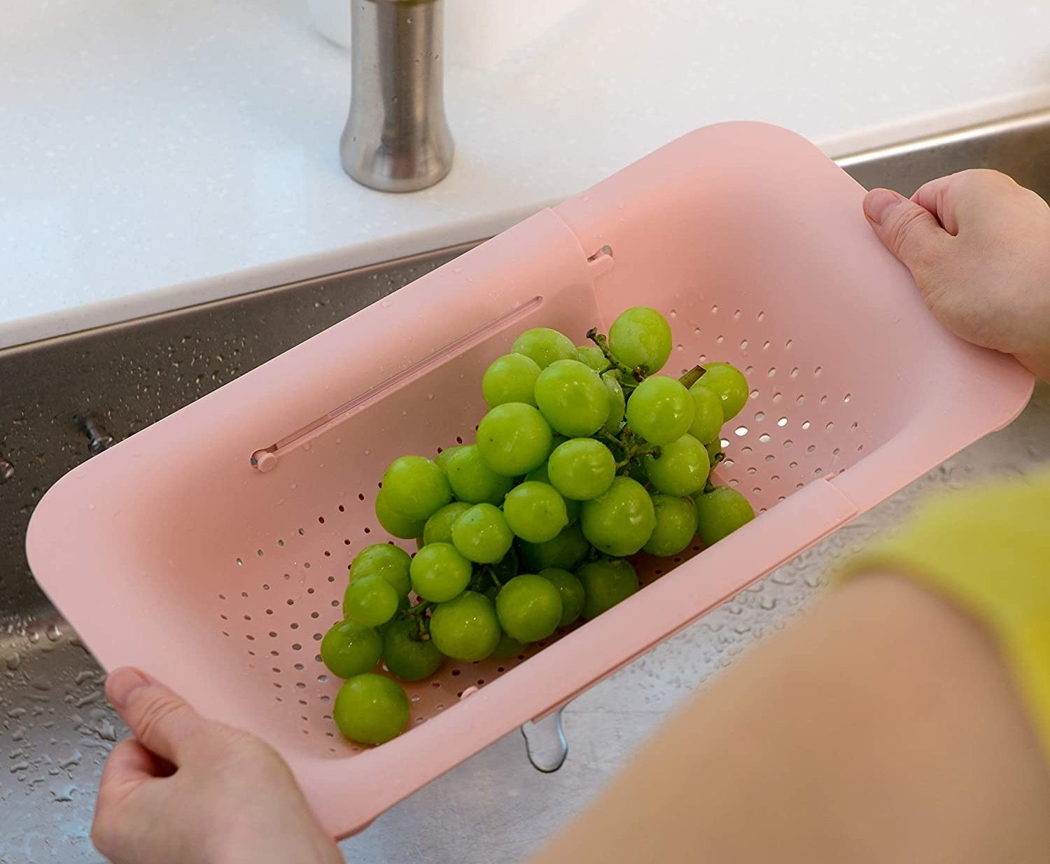 person drying grapes with the colander