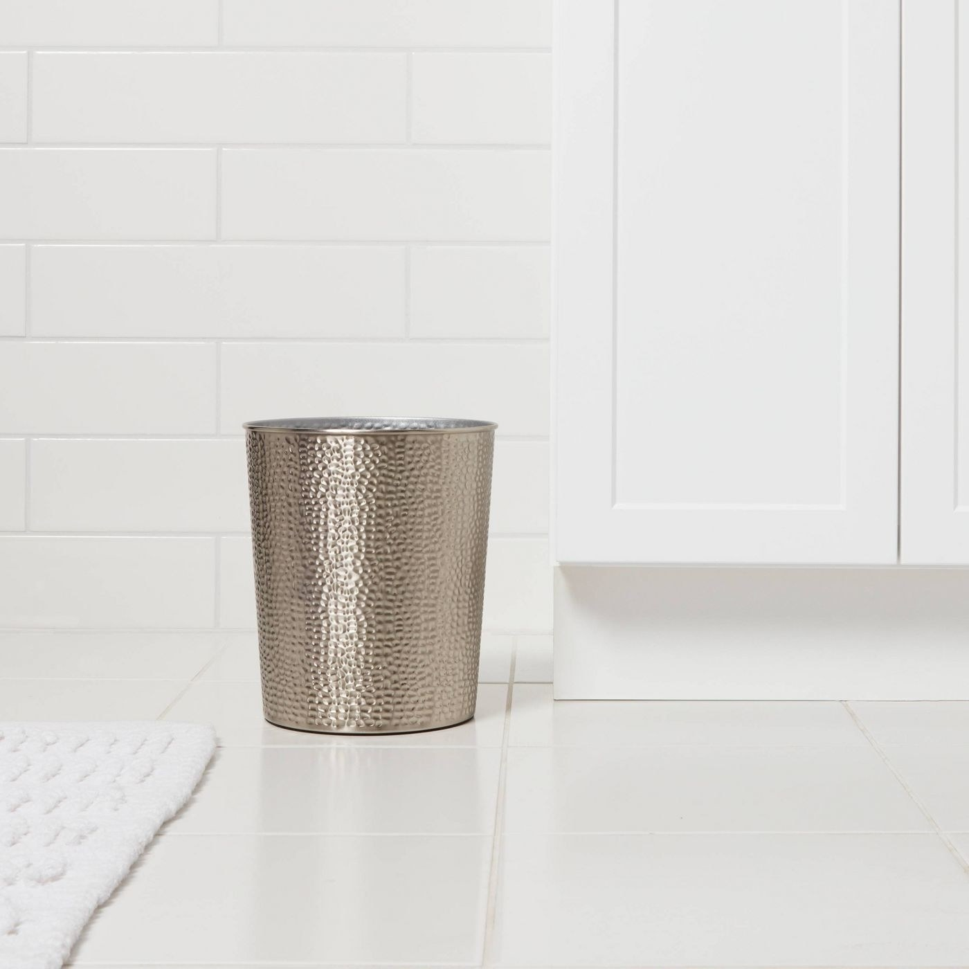 Silver trashcan on a white floor beside a white cabinet