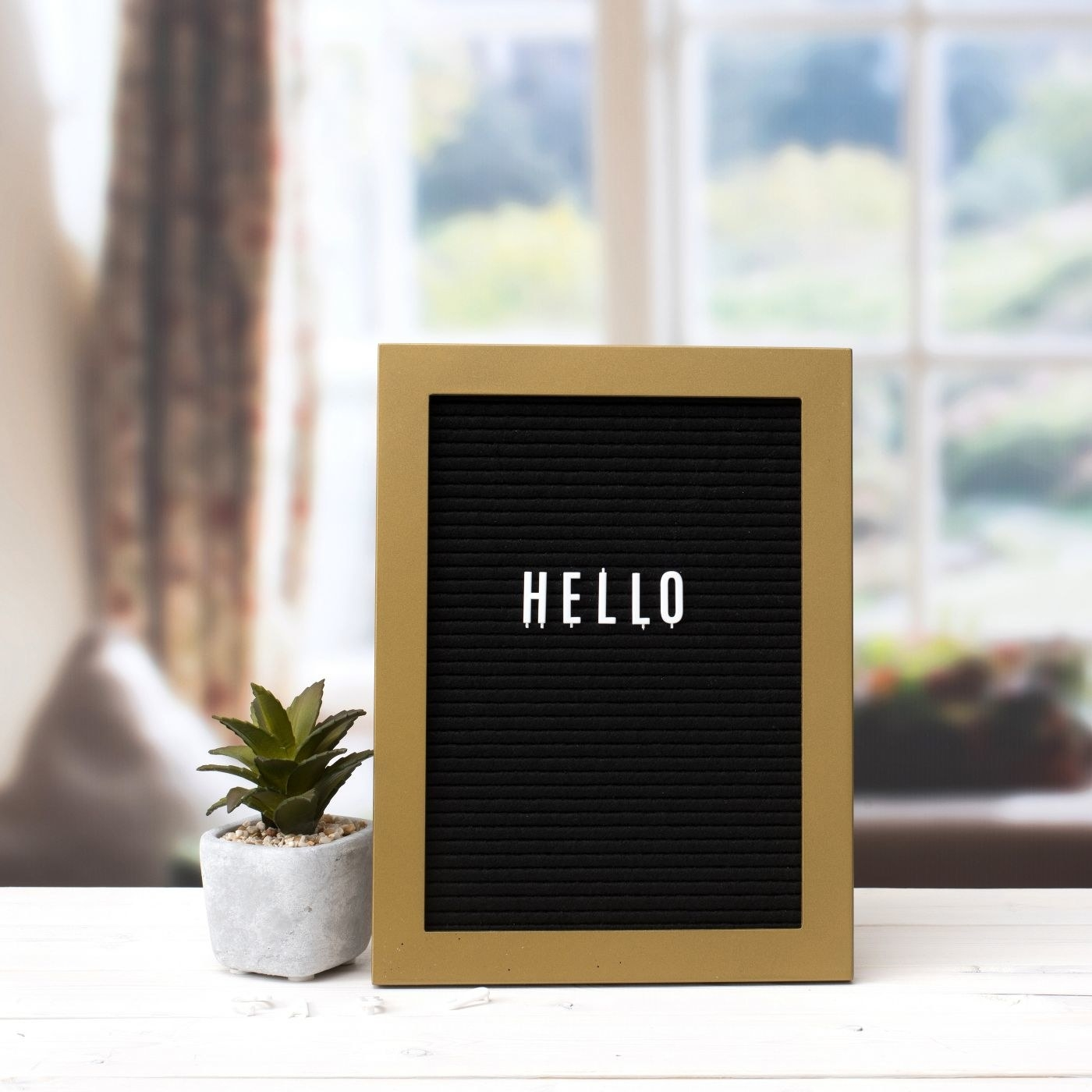 Black letterboard with white letters and gold frame beside a tiny green plant