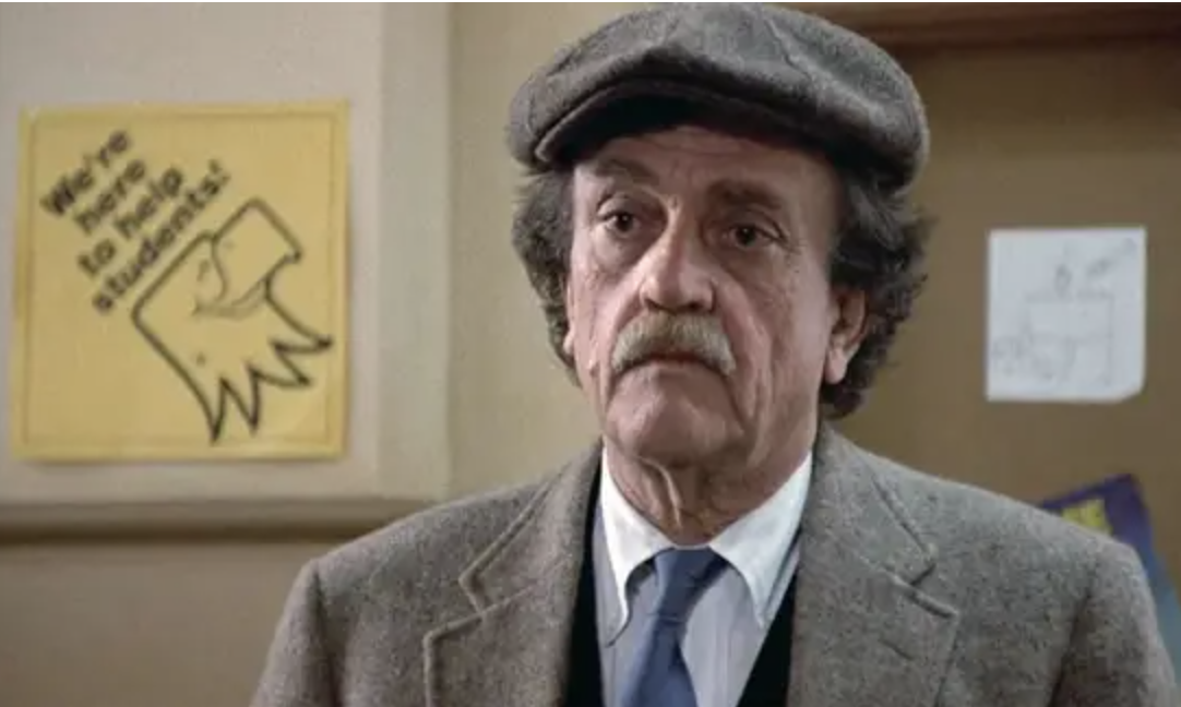 Kurt Vonnegut in a college hallway wearing a twead cap and suit