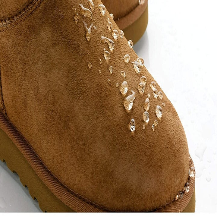 A suede boot with water droplets sitting on the surface