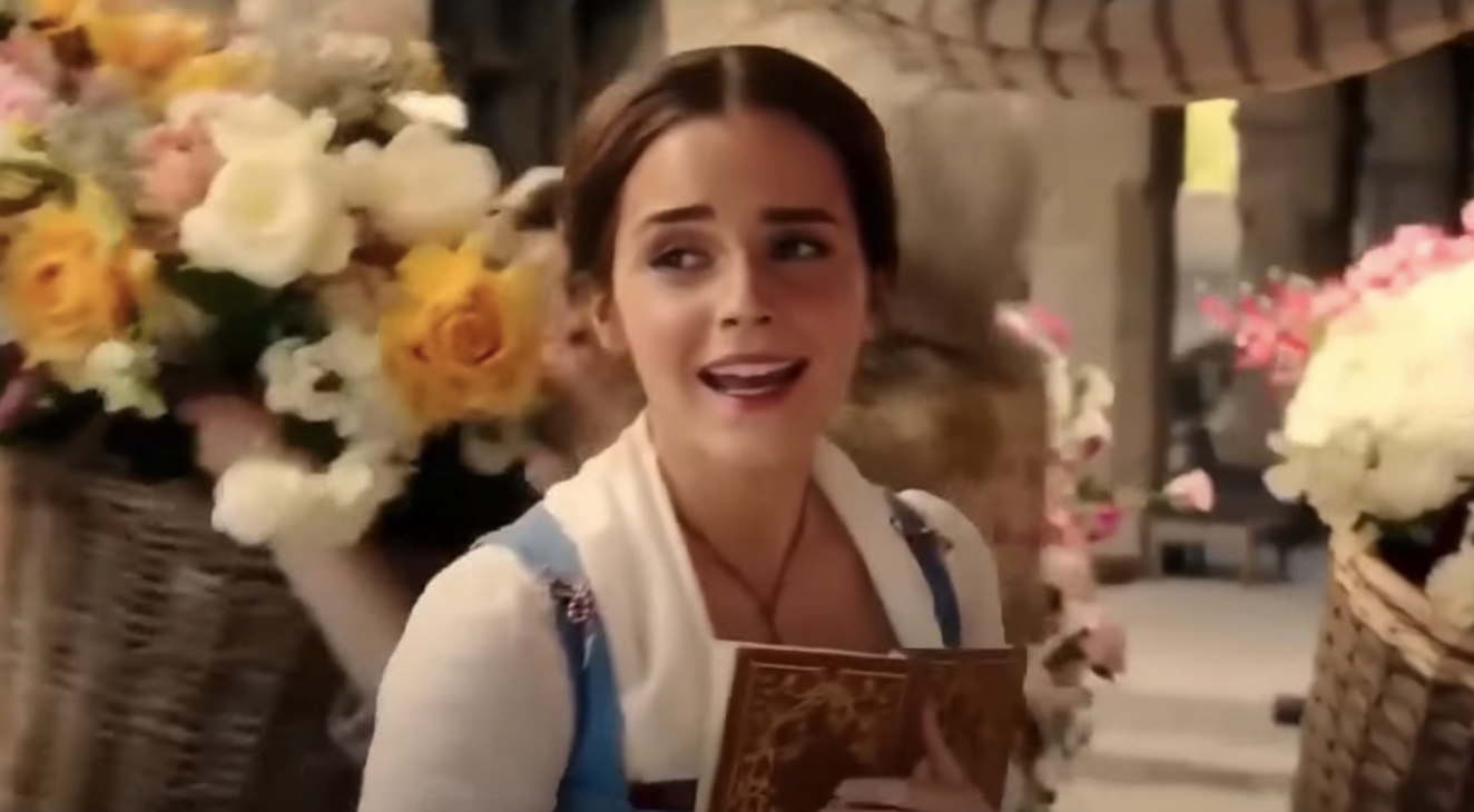 "Belle from ""Beauty and the Beast"" (2017) singing through the village while carrying a book"