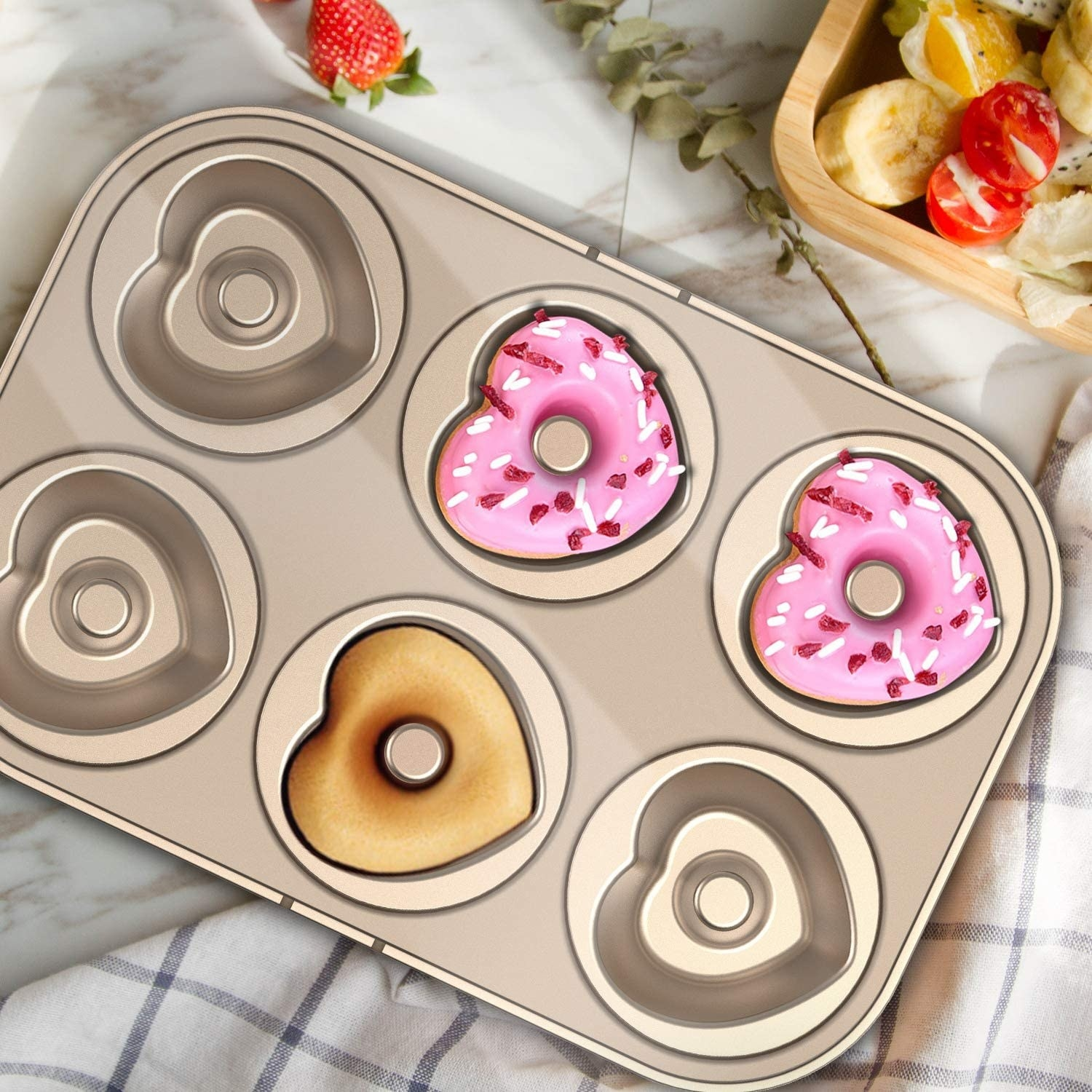 Two frosted donuts and one plain donut in the pan