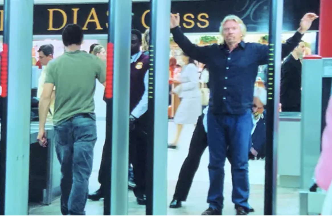 Richard Branson has his arms raised as he goes through airport security