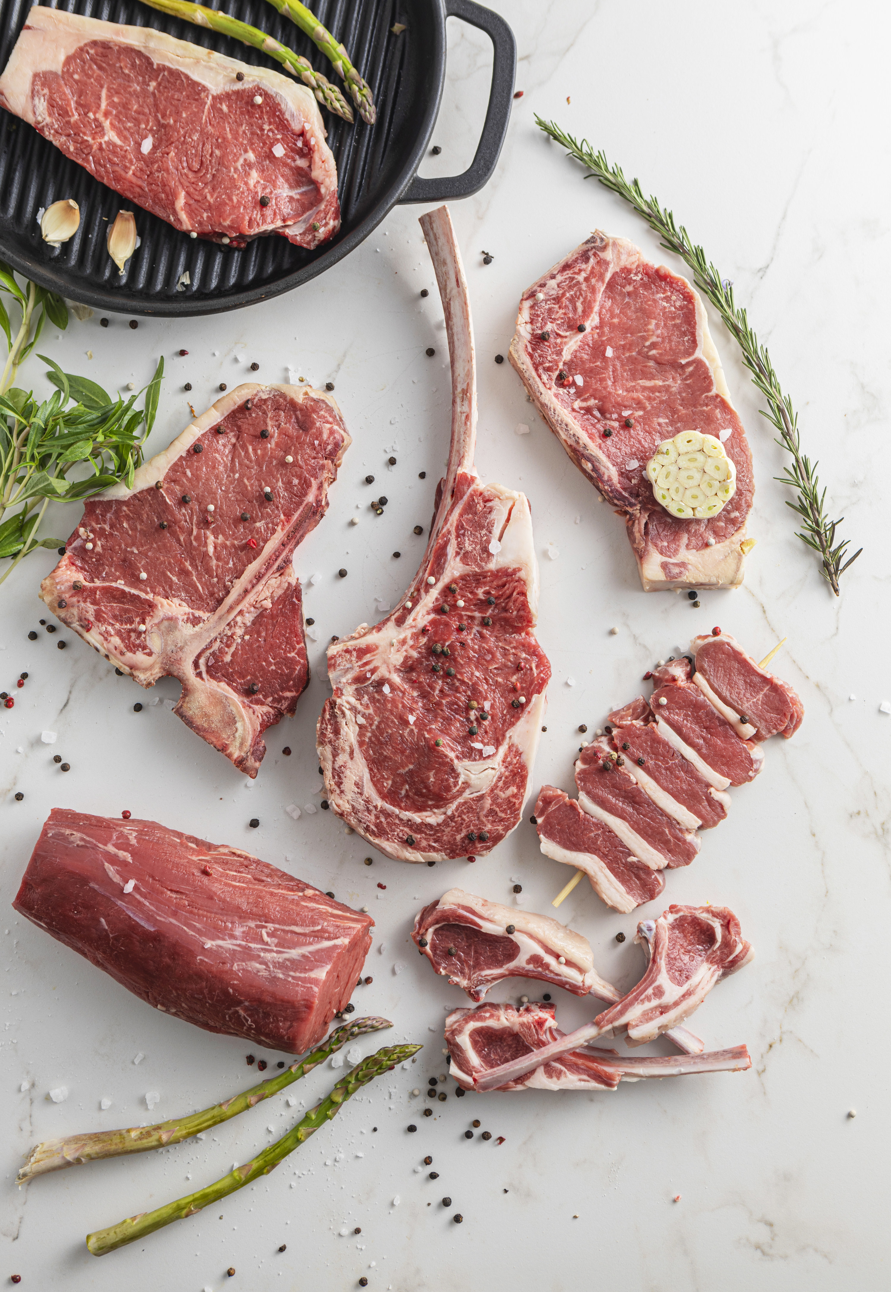 raw beef meat steaks for grilling with seasoning and utensils on marble background