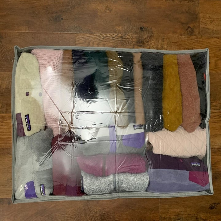 reviewer photo showing the underbed storage container neatly packed with sweaters and sweatshirts