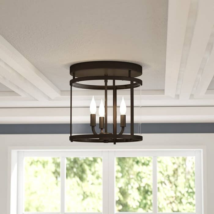The light, which is cylindrical glass with a dark bronze frame, and a base with three narrow bulbs extending from it
