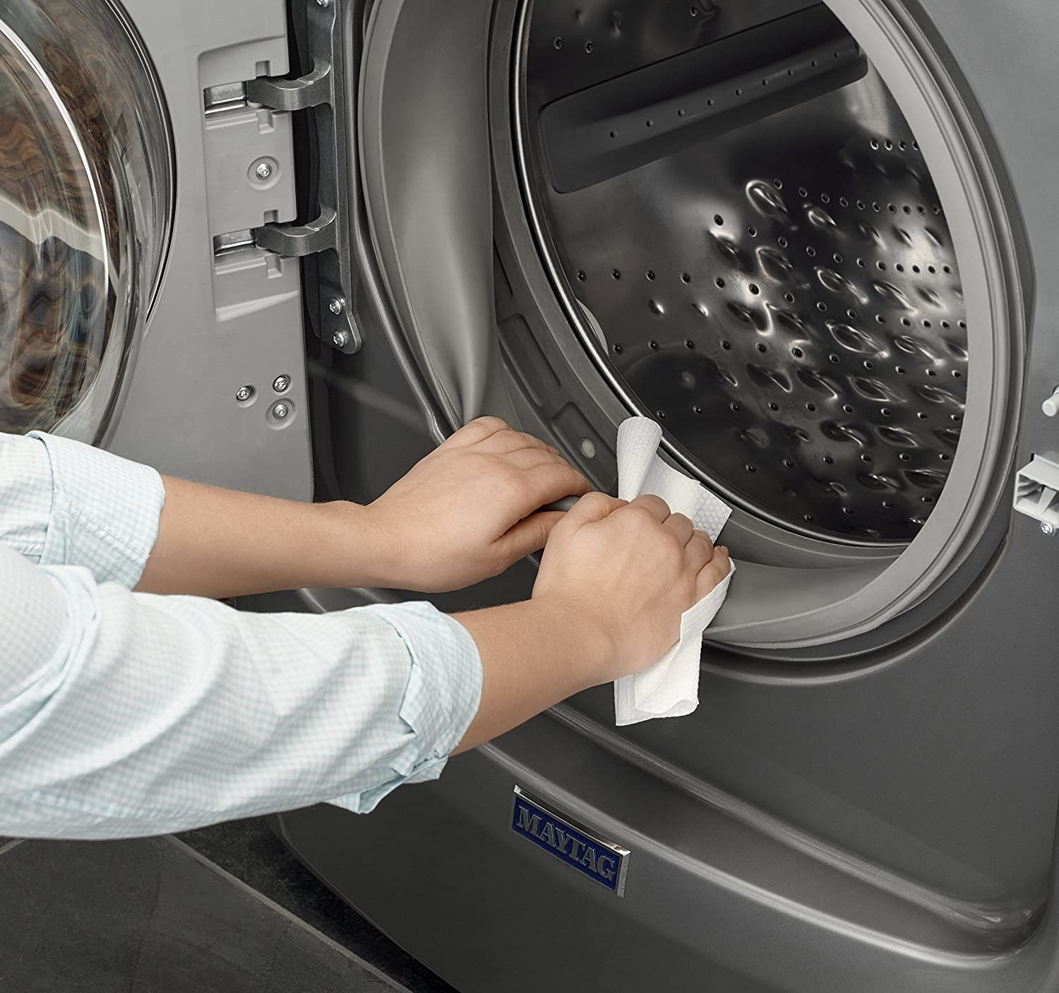 person wiping the inside of their dryer