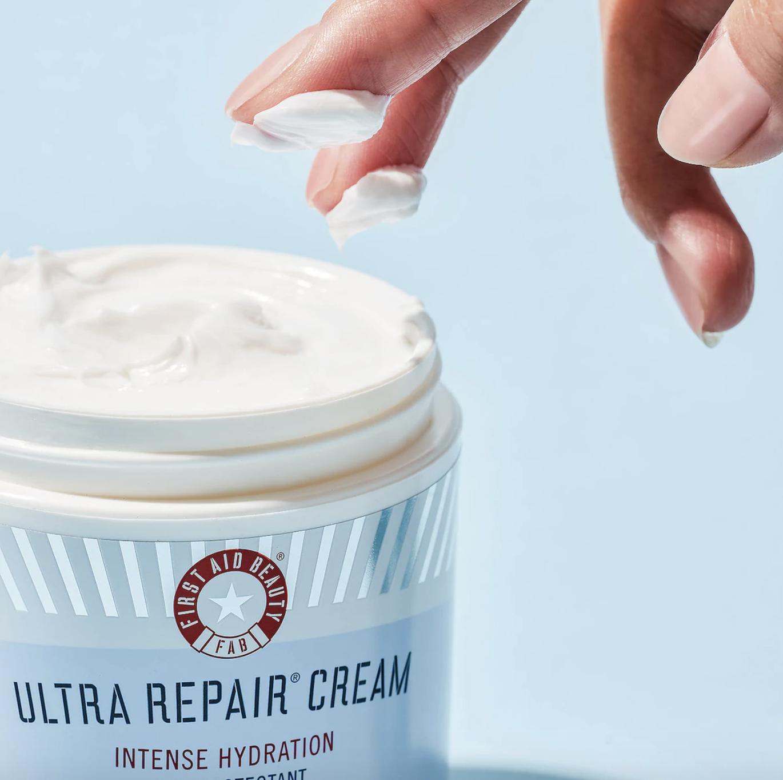 a model's hand reaches into a tub of the ultra repair cream