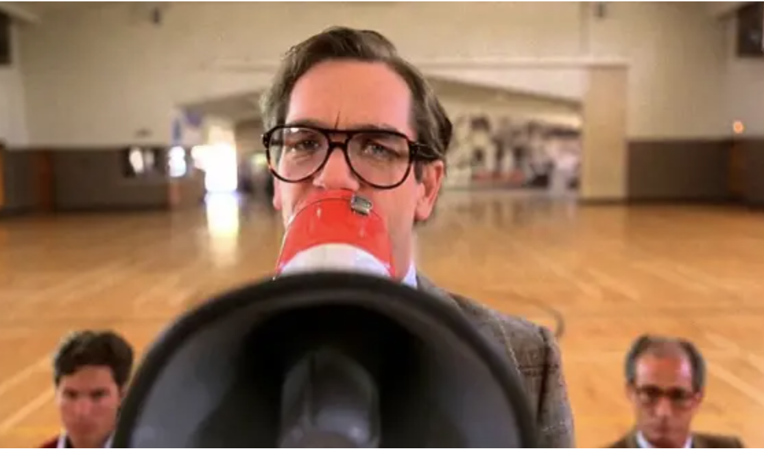 A straight-laced looking Huey Lewis holds up a bullhorn in a gymnasium