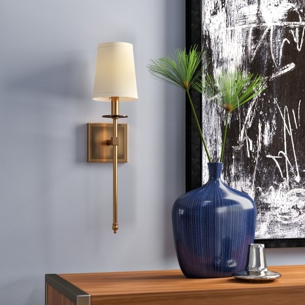 The sconce, which has a square base mounted to the wall, a long, thin lamp hand which extends from the base, and a small cream cloth shade at the top