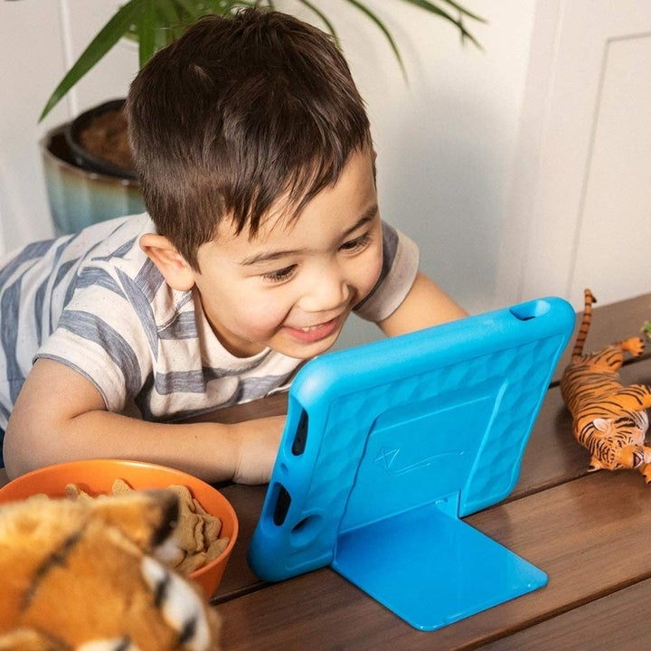 kid looking at the propped-up tablet