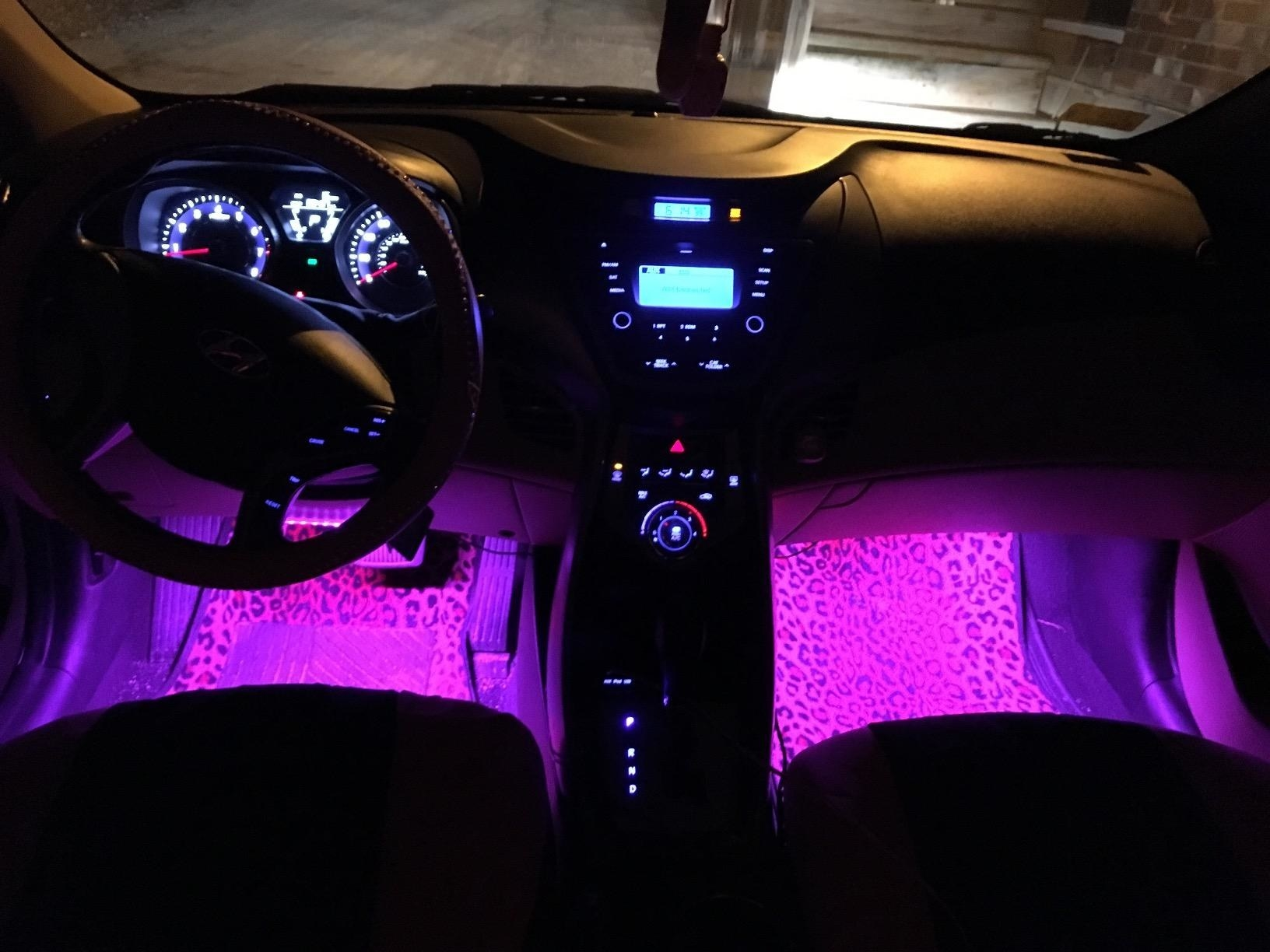 Reviewer photo of their car with the pink lights under the dashboard