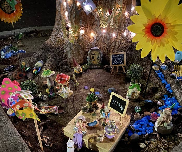 The base of a tree surrounded by twinkle lights, colorful rocks and fairy figurines