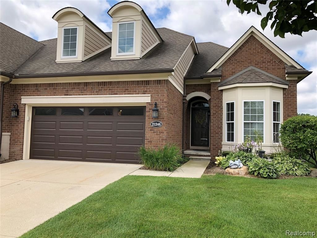 Brick house with garage on a manicured lawn