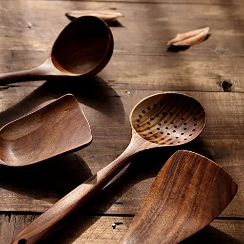 A wooden ladle, two spatulas, and a straining spoon