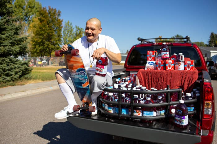 A grinning man sits in a pickup truck's bed, holding a skateboard and surrounded by bottles of cranberry juice