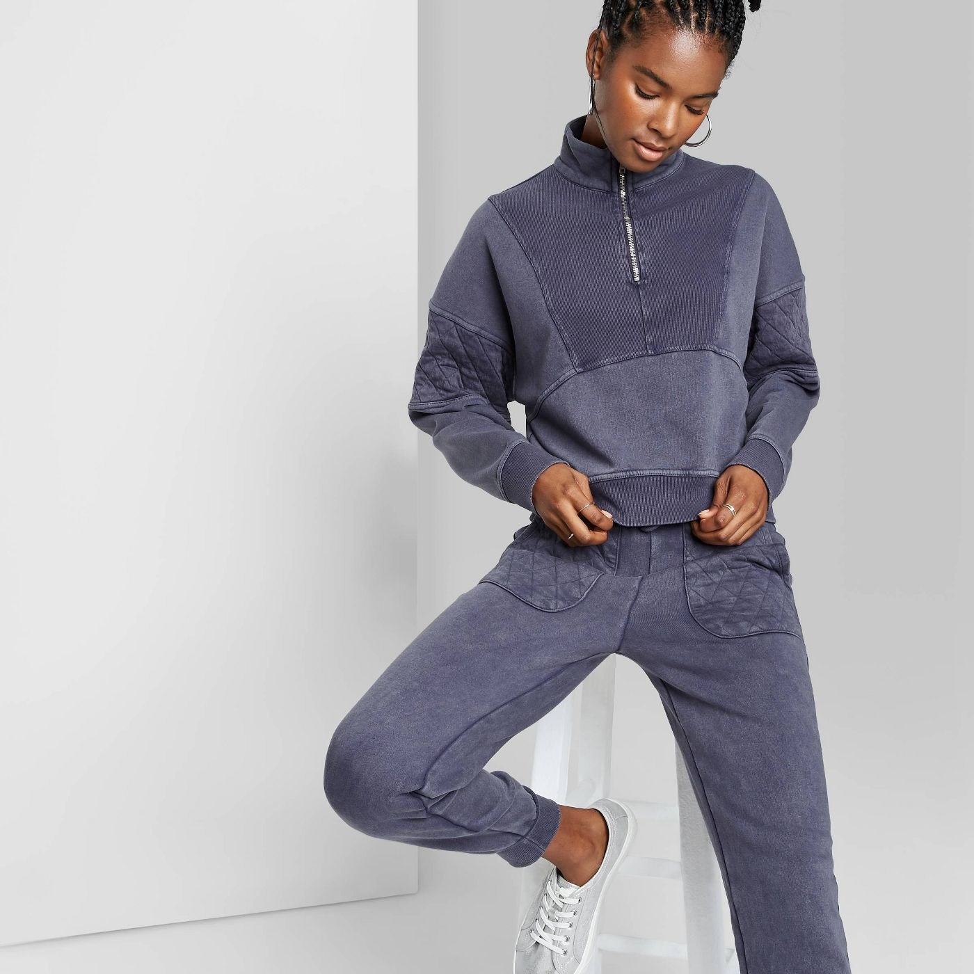 Model in quarter zip quilted sleeve pullover