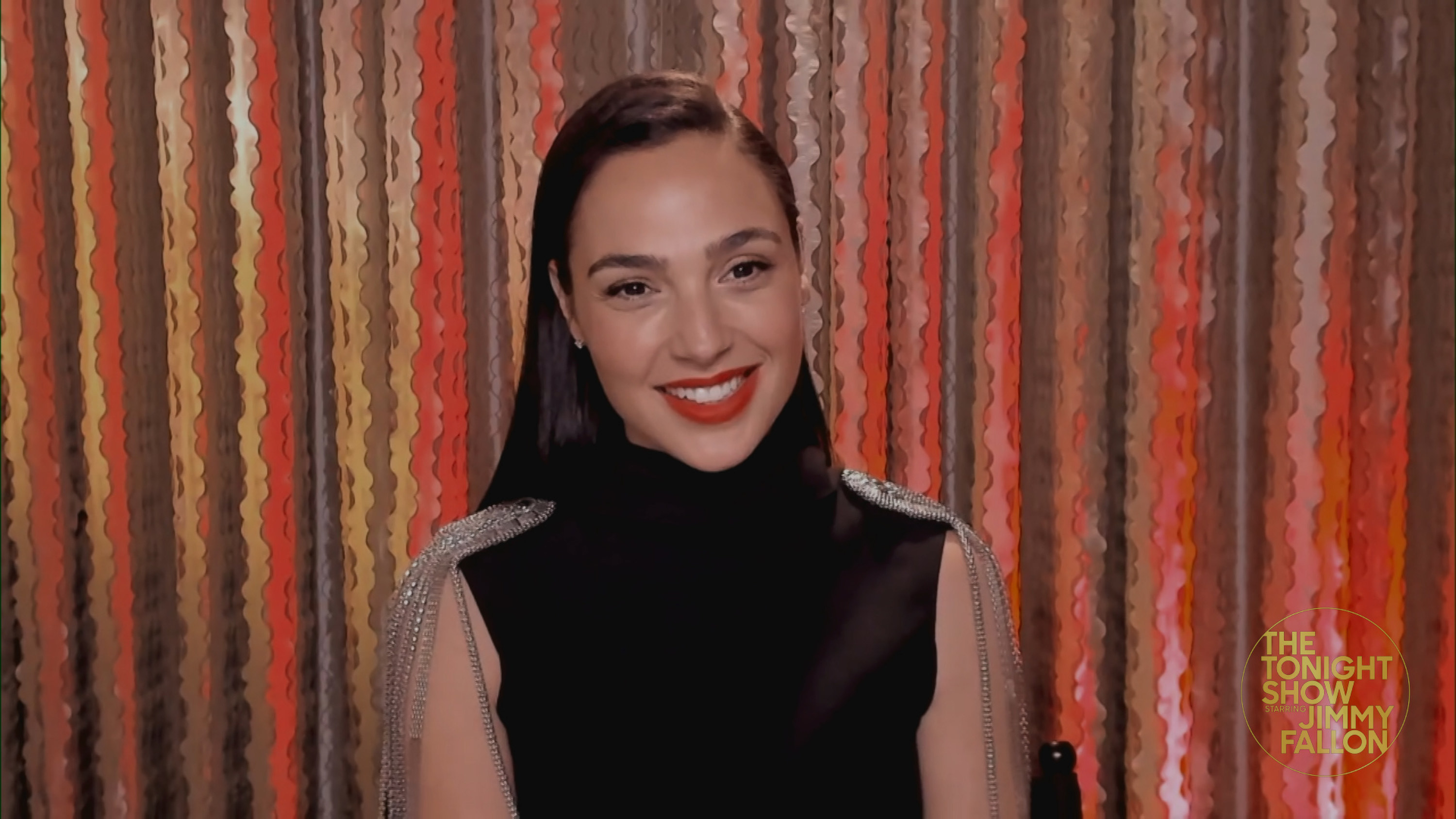 Gal Gadot smiles in front of a red-laced curtain