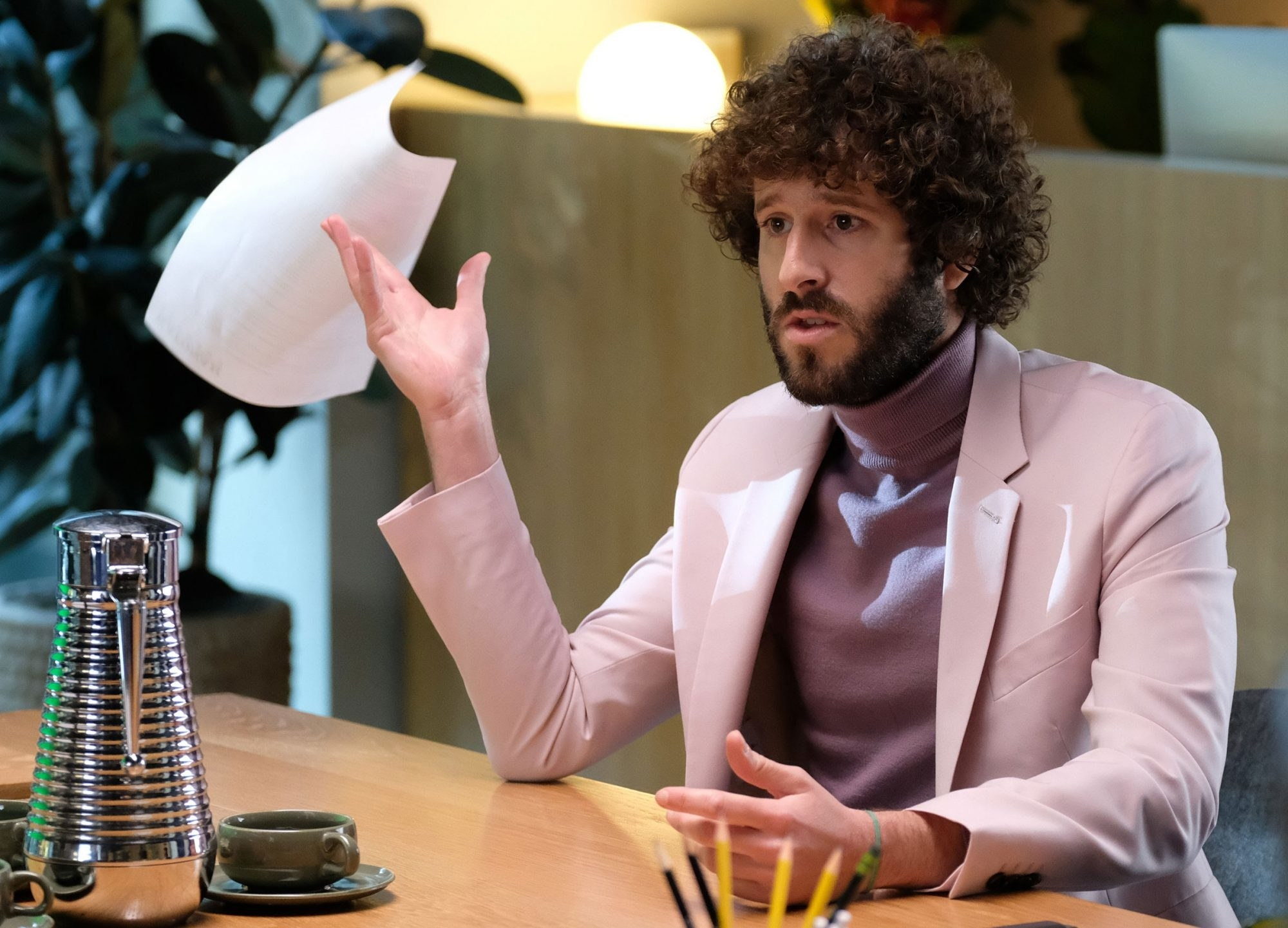 "Lil Dicky in ""Dave""; he is sitting in an office, talking to someone off-camera"