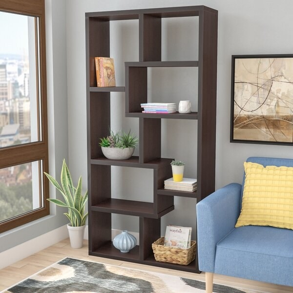 The bookcase, which is made from brown wood and has an open back; each shelf, rather than being straight across, are made of interlocking square areas