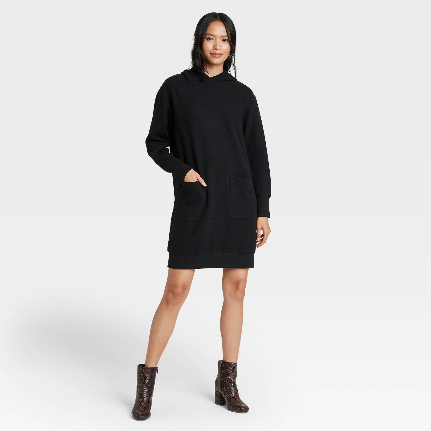 Model in black long sleeve sweater dress