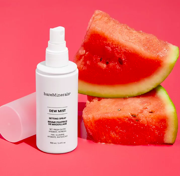 the dew mist setting spray in a white bottle with two slices of watermelon in the background
