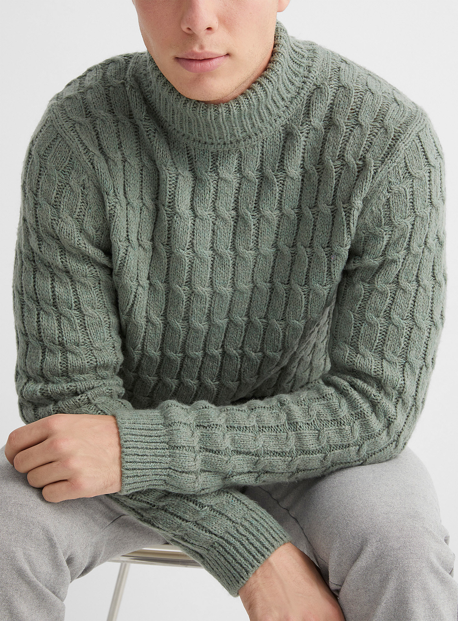 A person wearing a chunky knit sweater